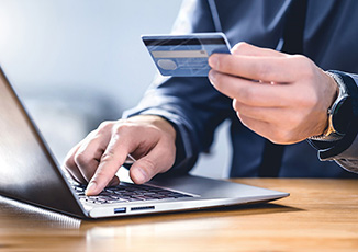 Man holding credit card while making purchase online